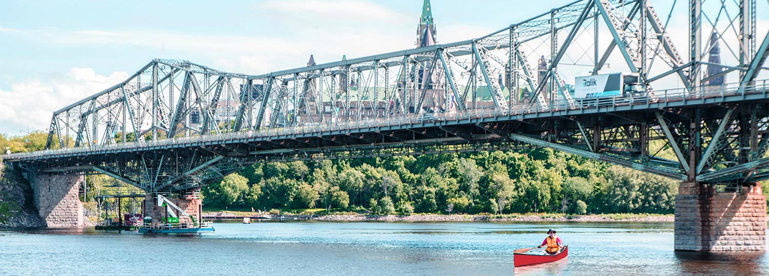 Man canoeing in Ottawa river, with Alexandra bridge in background, during a summer day.